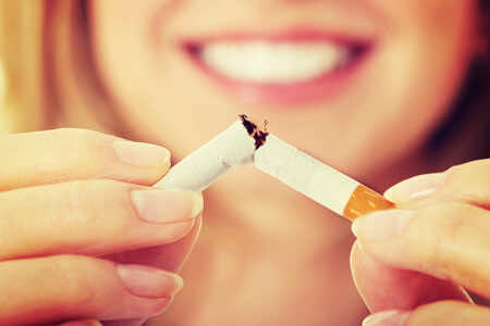 smiling woman breaking cigarette in half quit smoking