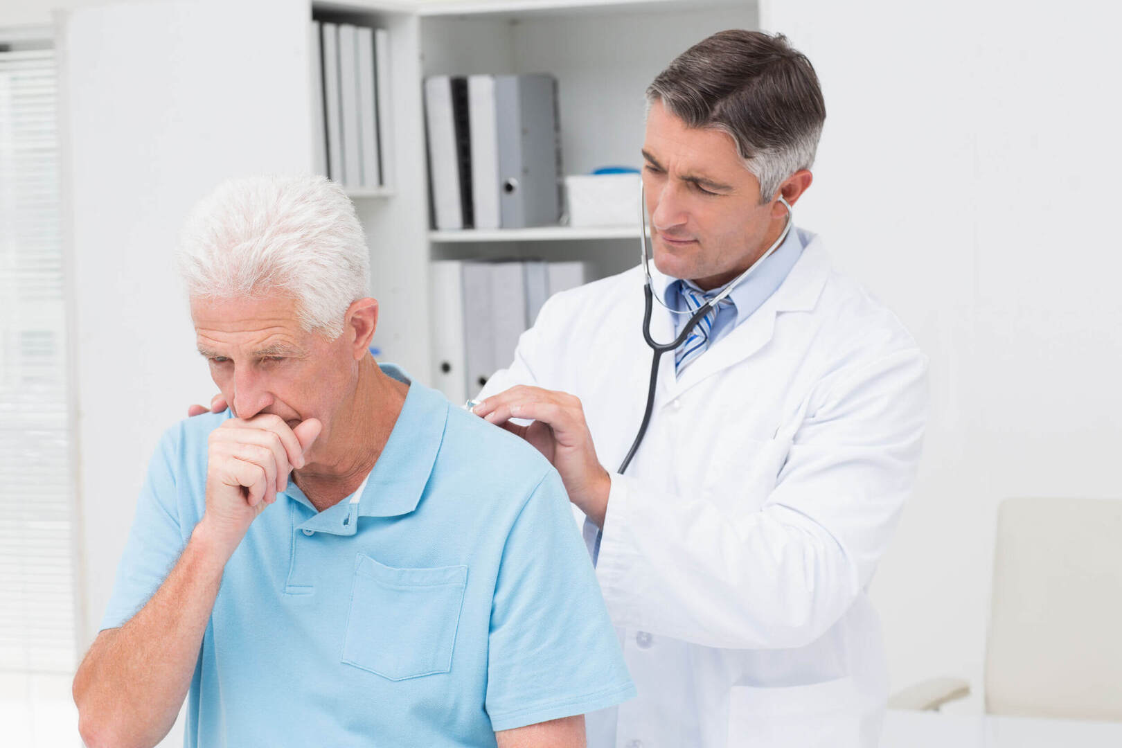 Older coughing patient checking in with doctor